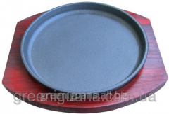 Frying pan cast iron on a wooden support a circle