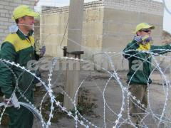 Installation of mesh fences from a barbed wire,